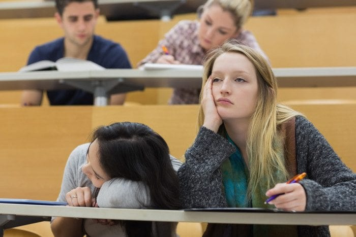 Bored student in a classroom. Her classmate is sleeping nearby.