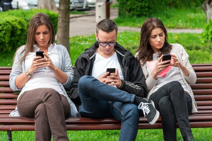 Three people sitting at the park using mobile phones. One man and two women.