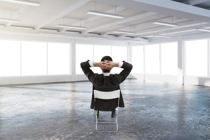 Businessman lean back sitting in a chair in a spacious room, while crossing his hand behind his head