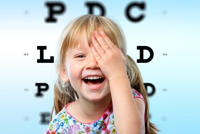 A child is laughing while blocking one of her eyes.