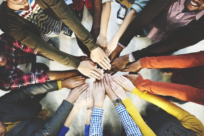 people bring their hands together in a circle