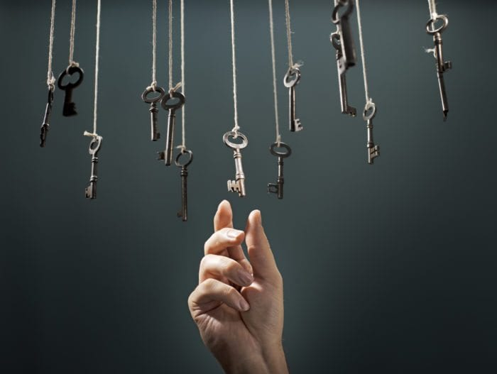 a hand picking a key from a lot of keys hanging from above