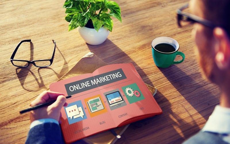 Business Man writing on an Online Marketing book
