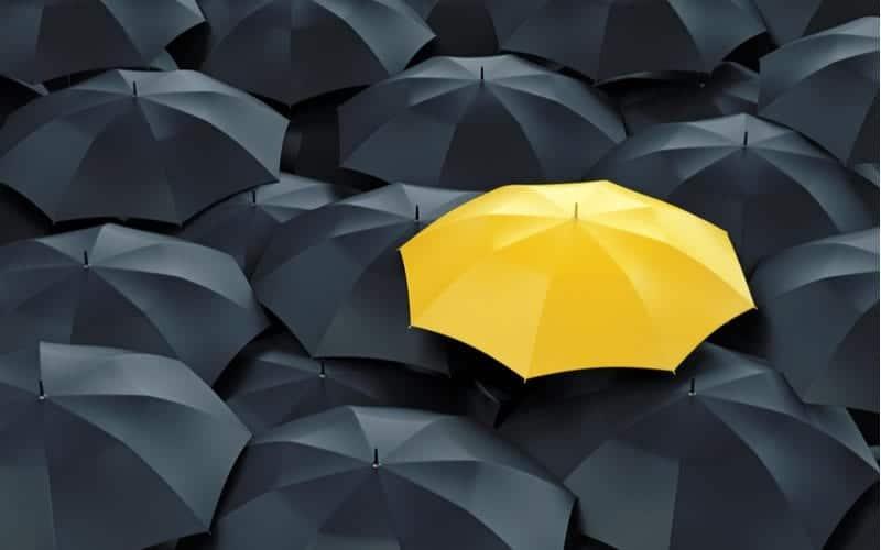 yellow umbrella that sticks out among black umbrellas